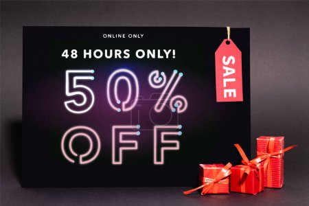 Photo for Placard with online only, 48 hours only, 50 percent off lettering and sale tag near presents on dark background - Royalty Free Image