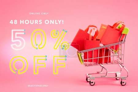 Photo for Shopping bags in small trolley near online only, 48 hours only, 50 percent off, select styles only lettering on pink, black friday concept - Royalty Free Image