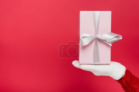 Photo for Cropped view of woman in white glove holding present isolated on red - Royalty Free Image