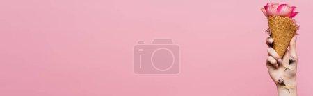 Photo pour Vue partielle de la femme tenant un cône de gaufre avec des pétales à la main avec des fleurs recouvertes de plâtres isolés sur rose, bannière - image libre de droit