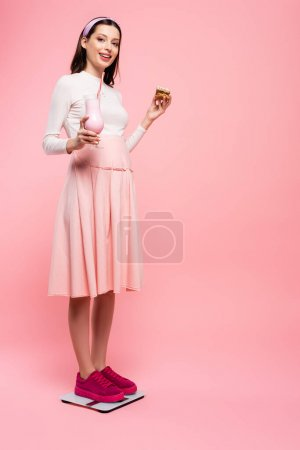 Photo for Young pretty pregnant woman with cake and milkshake on scales isolated on pink - Royalty Free Image