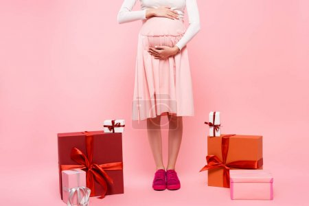 Photo for Cropped view of young pretty pregnant woman with presents isolated on pink - Royalty Free Image