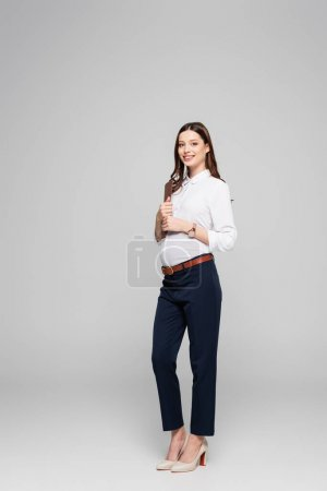 smiling young pregnant businesswoman with folder isolated on grey