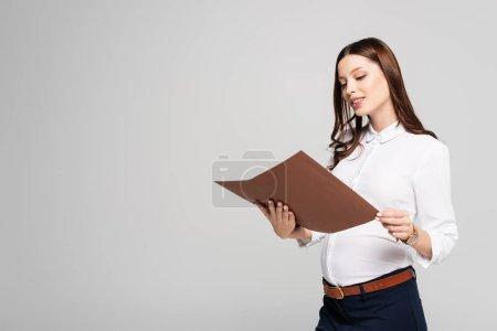 Lächelnde junge schwangere Geschäftsfrau mit Mappe in grau