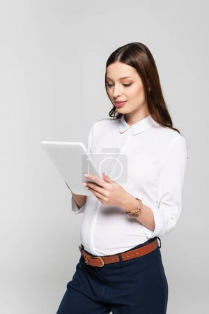 young pregnant businesswoman with digital tablet isolated on grey