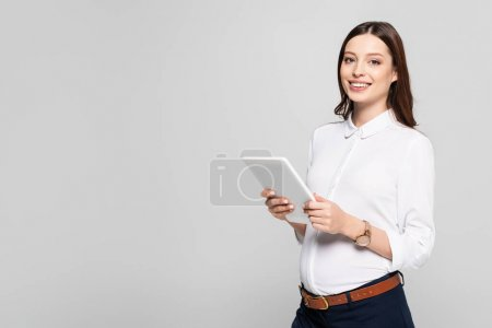 smiling young pregnant businesswoman with digital tablet isolated on grey