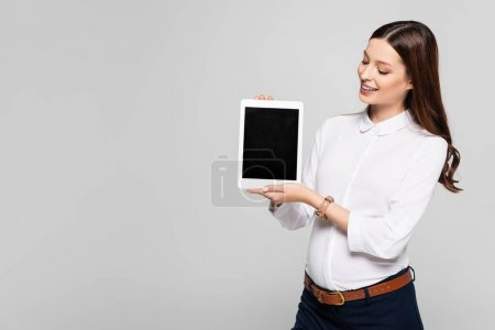 Photo for Smiling young pregnant businesswoman presenting digital tablet isolated on grey - Royalty Free Image