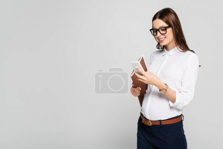 smiling young pregnant businesswoman in glasses with folder and smartphone isolated on grey
