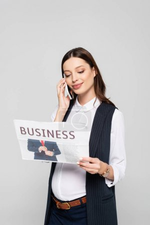 young pregnant businesswoman holding business newspaper and talking on smartphone isolated on grey