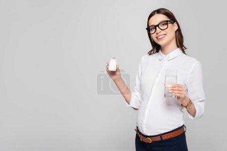 Photo pour Souriant jeune femme d'affaires enceinte dans des lunettes avec un verre d'eau et des vitamines prénatales isolées sur gris - image libre de droit