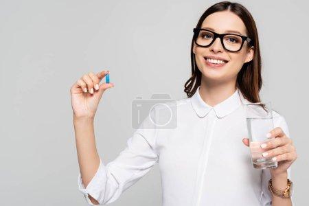 Lächelnde junge schwangere Geschäftsfrau in Gläsern mit Glas Wasser und Pränataltablette isoliert auf grau