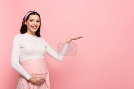 happy young pretty pregnant woman touching belly and pointing aside isolated on pink