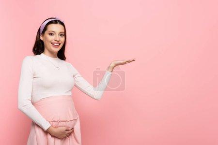 glücklich junge hübsche schwangere Frau berührt Bauch und zeigt zur Seite isoliert auf rosa