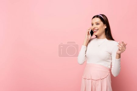 happy young pretty pregnant woman talking on smartphone isolated on pink