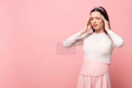 joven bonita mujer embarazada que sufre de dolor de cabeza aislado en rosa