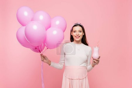 Photo for Happy young pretty pregnant woman with balloons and milkshake isolated on pink - Royalty Free Image