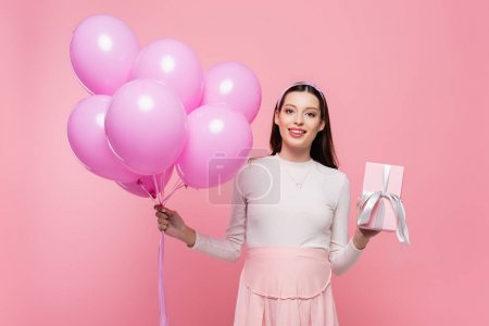 happy young pretty pregnant woman with balloons and gift isolated on pink