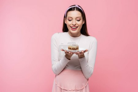 happy young pretty pregnant woman with cake isolated on pink
