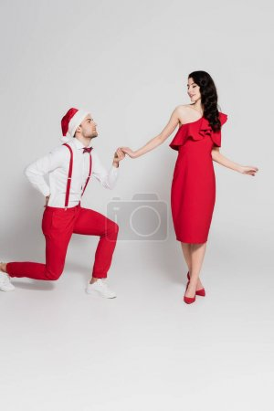 Man in santa hat standing on one knee and holding hand of smiling woman in red dress on grey background