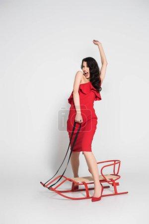 Photo pour Femme excitée en robe et talons debout près du traîneau sur fond gris - image libre de droit