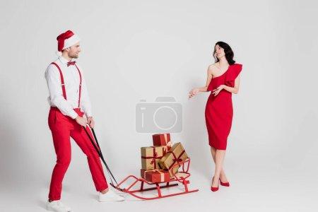 Photo pour Homme au chapeau de Père Noël debout près du traîneau avec des cadeaux et femme souriante en robe sur fond gris - image libre de droit