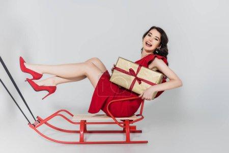 Photo pour Femme joyeuse en robe rouge et talons tenant présent tout en étant assis sur traîneau sur fond gris - image libre de droit