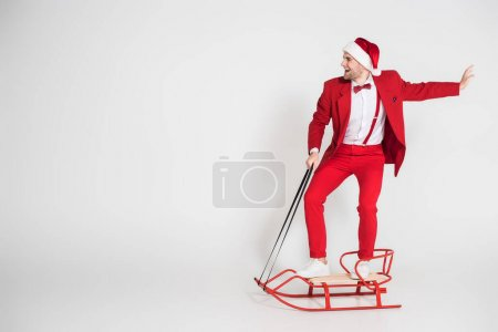 Photo for Cheerful man in santa hat and red suit standing on sleigh on grey background - Royalty Free Image