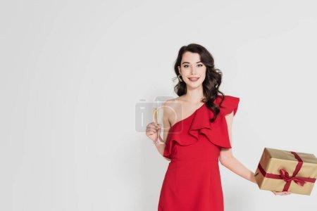 Lächelnde Frau in rotem Kleid mit Glas Champagner und Geschenk in grau