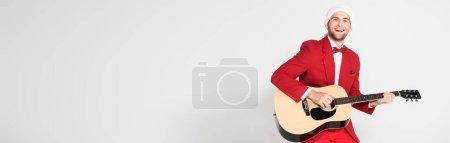 Photo pour Joyeux homme au chapeau de Père Noël jouant de la guitare acoustique sur fond gris, bannière - image libre de droit