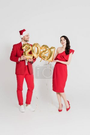 Brunette woman in red dress holding balloons in shape of 2021 numbers near man in santa hat on grey background