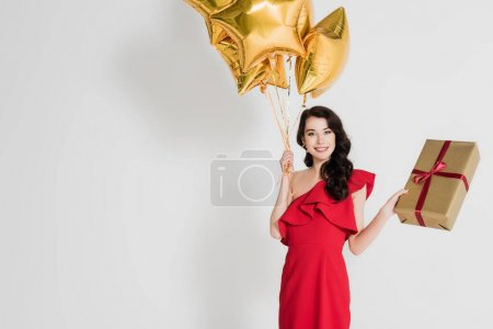 Photo for Smiling woman holding balloons and gift box on grey background - Royalty Free Image