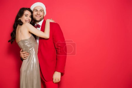 Brunette woman in dress hugging boyfriend in santa hat on red background