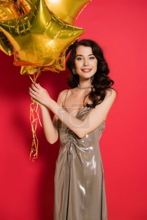 Brunette woman in dress smiling at camera while holding balloons on red background