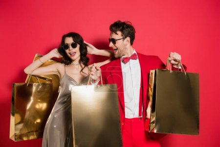 Stylish man in sunglasses holding shopping bags near cheerful girlfriend on red background