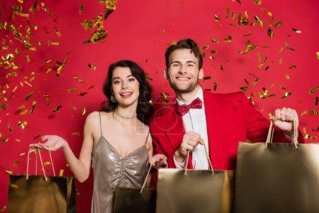 Photo pour Couple élégant tenant des sacs à provisions sous confettis tombant sur fond rouge - image libre de droit