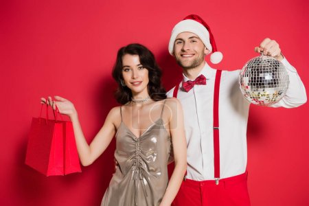 Smiling woman holding shopping bags near boyfriend in santa hat with disco ball on red background