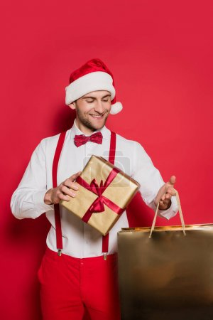 Photo for Cheerful man in santa hat holding shopping bag and present on red background - Royalty Free Image