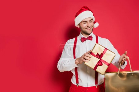 Photo for Positive man in santa hat holding gift box and shopping bag on red background - Royalty Free Image