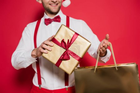 Photo for Cropped view of gift box and shopping bag in hands of smiling man blurred on red background - Royalty Free Image
