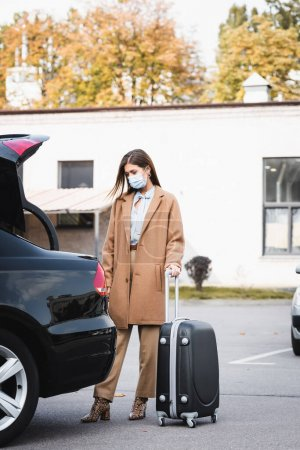 woman in medical mask and stylish autumn outfit standing near open car trunk with suitcase