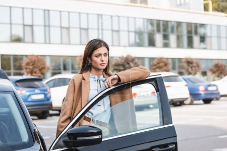 Photo for Thoughtful young woman in trench coat looking away while leaning on car door - Royalty Free Image