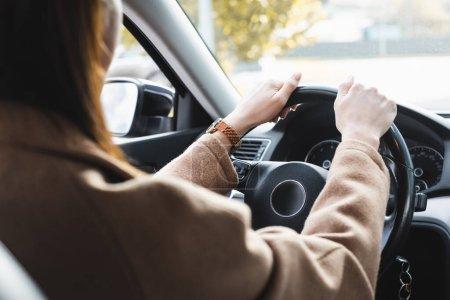 Frau, die Auto fährt, auf unscharfem Vordergrundbild beschnitten