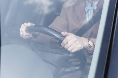 Ausgeschnittene Ansicht einer Frau mit Lenkrad während der Autofahrt auf verschwommenem Vordergrund