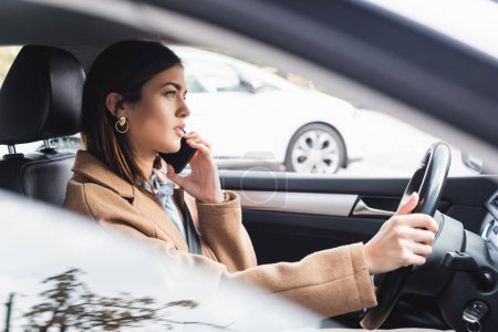 Photo for Side view of stylish woman in trench coat talking on mobile phone while driving car on blurred foreground - Royalty Free Image
