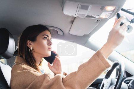 Photo pour Jeune femme ajuster rétroviseur tout en parlant sur smartphone en voiture - image libre de droit