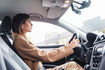 Photo pour Vue latérale de la femme en trench coat conduisant la voiture au premier plan flou - image libre de droit