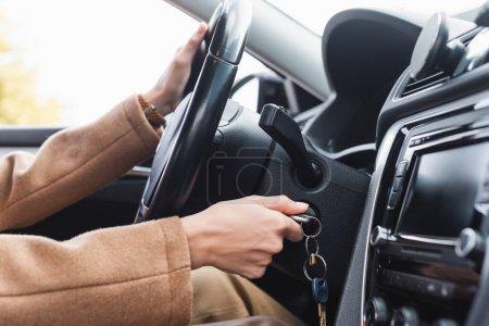 Photo pour Vue partielle de la femme démarrant la voiture tout en tenant le volant - image libre de droit