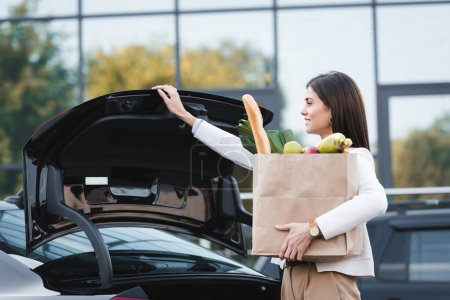 Photo for Smiling woman opening car trunk while holding shopping bag with food - Royalty Free Image