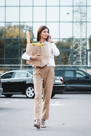 stylish woman talking on smartphone while walking along car parking with food in shopping bag