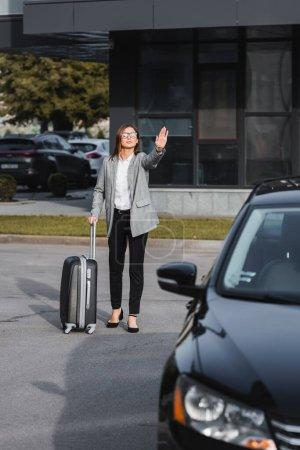 stylische Geschäftsfrau mit Koffer winkt Hand neben schwarzem Auto auf verschwommenem Vordergrund